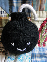 crocheted black bomb with smiley face on it