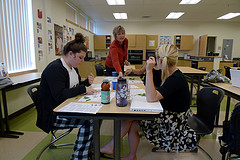 teacher at table talking to student