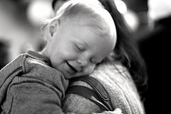 toddler hugging mom, smiling with joy
