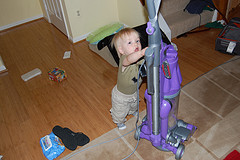 toddler trying to hold vacuum cleaner