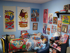 bedroom for a young boy with blue walls, lots of posters