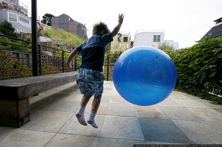 boy jumping in mid-air bouncing huge ball