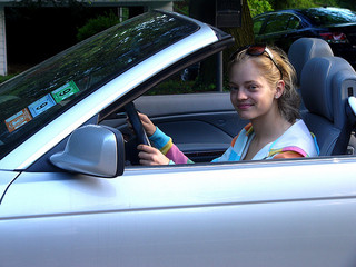 teen girl at wheel of blue car