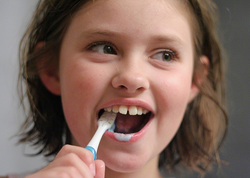 girl smiling and brushing teeth