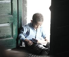 boy reading book in doorway