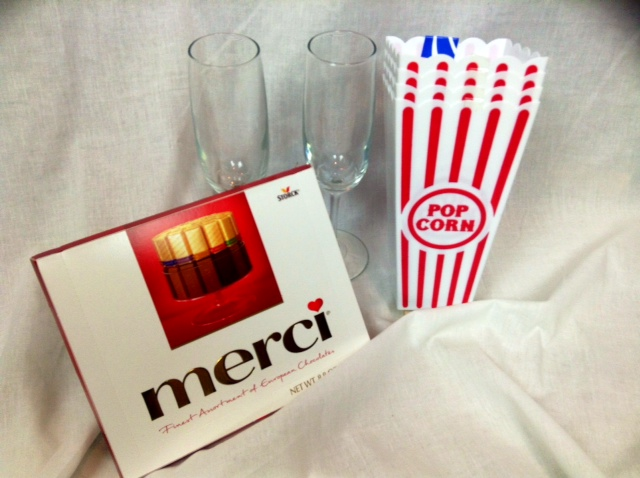 champagne flutes, popcorn buckets, and box of Merci chocolates.