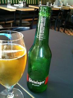 glass of beer in front of beer bottle