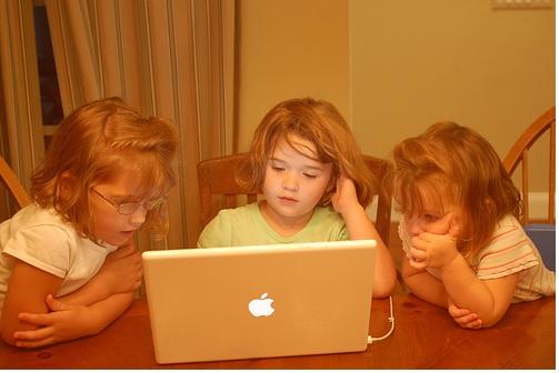 3 girls playing games on laptop computer