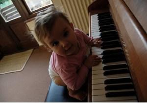 young toddler sitting at piano, looking at camera