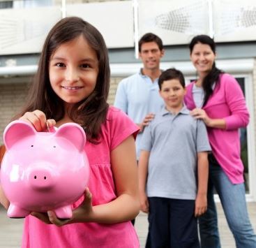 girl holding piggy bank, parents and brother standing behind