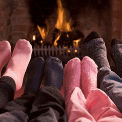 3 pairs of feet in front of cozy fire