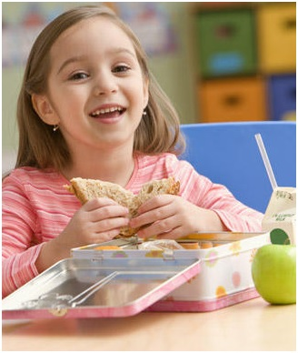 young girl eating out of lunchbox and smiling