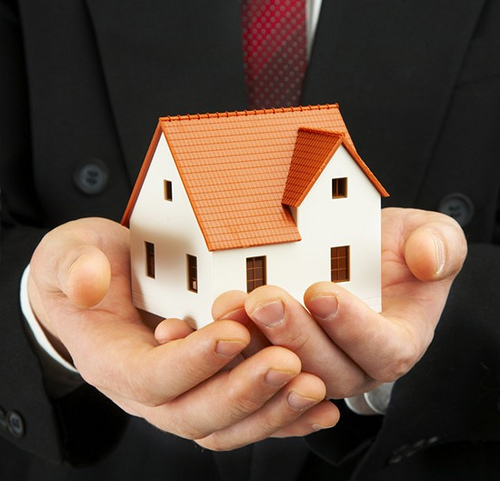 man holding model house in his hands
