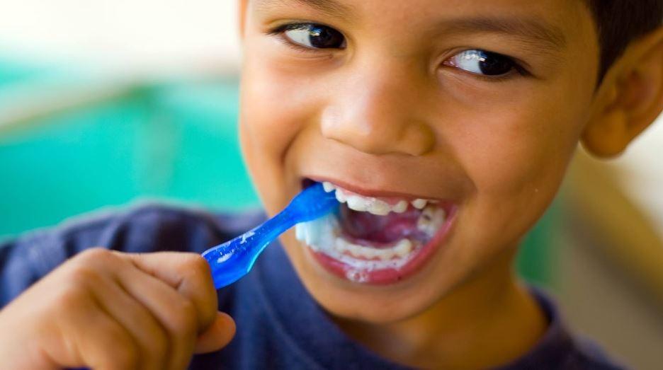 boy brushing teeth and smiling