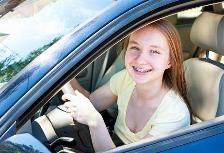 teen girl at wheel, smiling