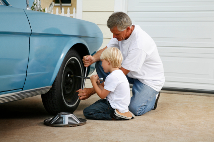 father helping son replace tire on car