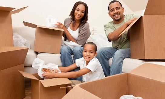 mom, dad, and son packing belongings into moving boxes
