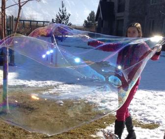 girl making giant bubble outside