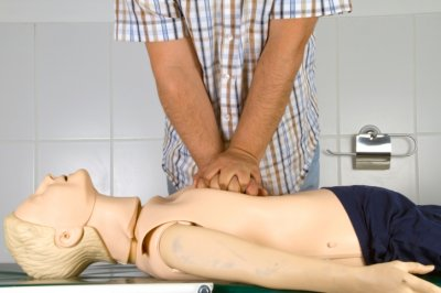 man practicing cpr on dummy