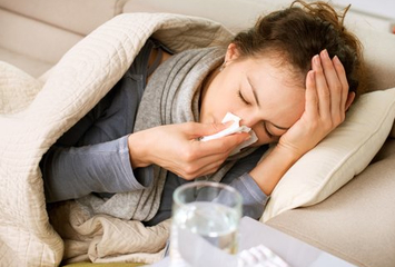 woman laying on couch, blowing nose