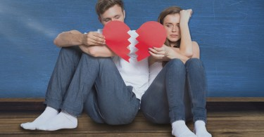 Young couple holding broken heart against blue room