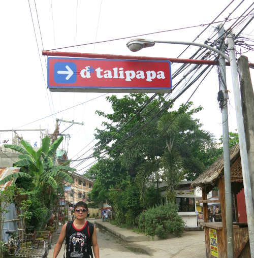 Evan standing under d'talipapa sign