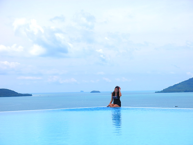 Raevian sitting on pool edge with gorgeous sea view