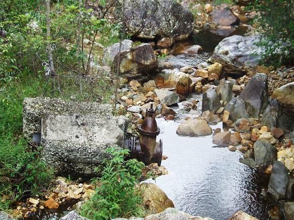 Restos do que sobrou de uma antiga barragem ainda se encontra em uma grande extensão do leito do Rio do Ouro
