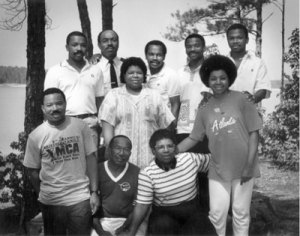 "Starting in rear-left: Bruce K. Jackson, Charles B. Jackson, Carl D. Jackson, Toney E. Jackson, E. Scott Jackson, (standing middle) Veronica R. Jackson, (front row) M. Don Jackson, (squatting) Carletha Jackson and Marian Jackson, and (standing) Carletta F. Smith. Photo from ""Celebrate '88,"" immediate family reunion (of Carletha and Marian Jackson off springs) at Hickory Knob State Park, SC in July 1988."