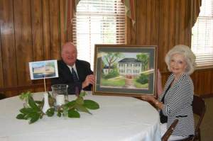 Rev. Barry Cannon and artist Virginia Culbertson hold a picture that Mrs. Culbertson painted of the Shepherd House that sat on the site where the new parsonage is located. The watercolor is painted after an oil painting by Florence Mims Bryan c. 1980. A photo taken by Cynthia Bull of the new parsonage sits on the table beside Rev. Cannon.