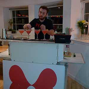 Meet William, our mixologist. Here, he's giving cosmopolitan's their final touches.