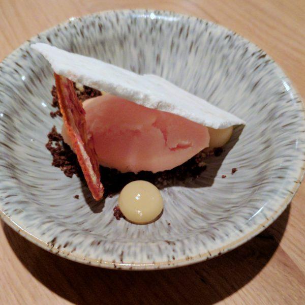 Pre-dessert: a shy quennel of bloor orange sorbet in a lean-to of meringue.