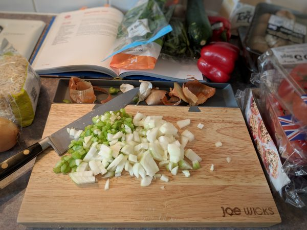 My tiny work surface may look a mess but this chopping board helps me keep things tidy.