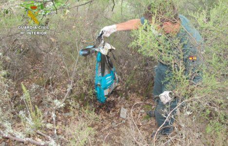 Uno de los agentes muestra el cadáver de un perro dentro de una bolsa