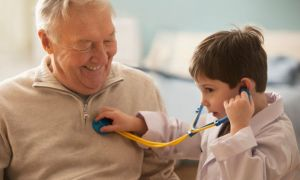 Caucasian boy listening to grandfather's heartbeat with stethoscope