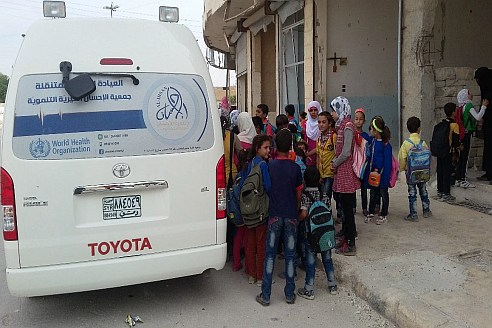 2 Syrian children line up at a WHO-supported mobile clinic in western Aleppo. With the introduction of the mobile clinics and in partnership with nongovernmental organizations, WHO has provided humanitarian health support to the under-served populations. This includes areas where the health care system has been adversely affected by the crisis especially Dar'a, Aleppo, Rural Damascus, Al Hassakeh and Deir ez-Zor among others.