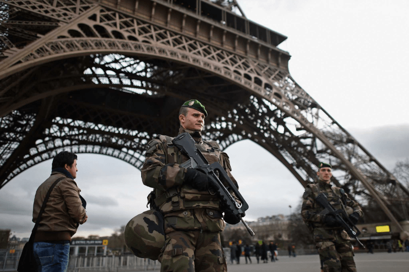 French troops stand guard at the Eiffel Tower, increasing regional security following the November 13th, 2015 Paris attacks.