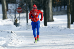 A man jogs around Lake Harriet in south Minneapolis in a Spiderman wind suit