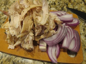 Shredded leftover chicken with some sliced onion, ready to toss in the pan.