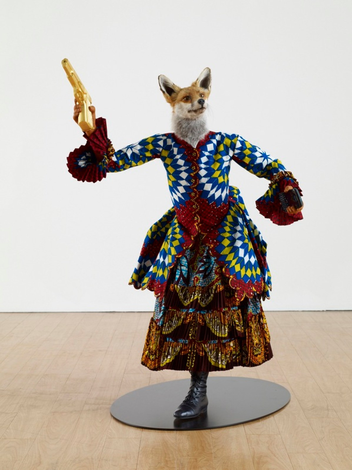 Yinka Shonibare MBE Revolution Kid (fox girl), 2012 Mannequin, Dutch wax printed cotton, fibreglass, leather, taxidermy fox head, steel base plate, BlackBerry and 24 carat gold gilded gun 111.8 x 91.4 x 76.2 cm Courtesy of the artist and James Cohan Gallery, New York and Shanghai