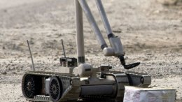"A U.S. Army explosive ordnance disposal (EOD) robot, ""i-Robot"", pulls the wire of an alleged improvised explosive device (IED), found by the Iraqi Police. U.S. Navy photo by Journalist 1st Class Jeremy L. Wood, Wikipedia Commons."