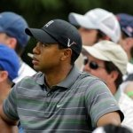 Tiger Woods watches K.J. Choi of South Korea's drive off the sixth tee during the first round of the Masters golf tournament in Augusta, Ga., Thursday, April 8, 2010.