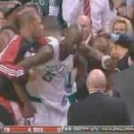 Boston center Kevin Garnett (white uniform) restrained after throwing elbow