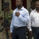 Wyclef Jean , center, walks surrounded by security at his mother's house in Croix de Bouquets, Haiti, Wednesday, Aug. 18, 2010.