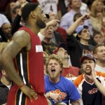 Cleveland Cavaliers fans yell at Miami Heat's LeBron James (L) during the fourth quarter of their NBA basketball game in Cleveland March 29, 2011