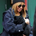Beyonce swaddles her daughter Blue Ivy Carter (b. January 7, 2012) in a black blanket as she leaves Sant Ambroeus restaurant in the West Village. (Feb. 26, 2012)