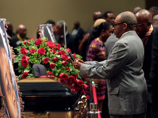 Spike Lee takes a photo of Michael Brown's cap atop his casket at