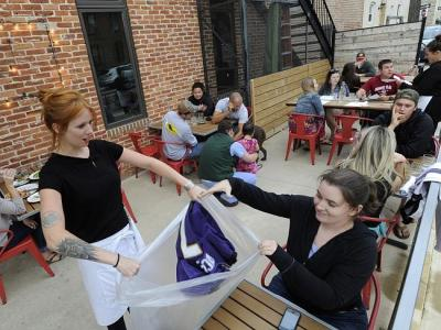 Hersh's Pizza bartender Abby Hopper collects a Ray Rice Baltimore Ravens football jersey from Erin McGonigle.
