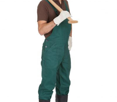 Happy young gardener in dungarees. Isolated on white