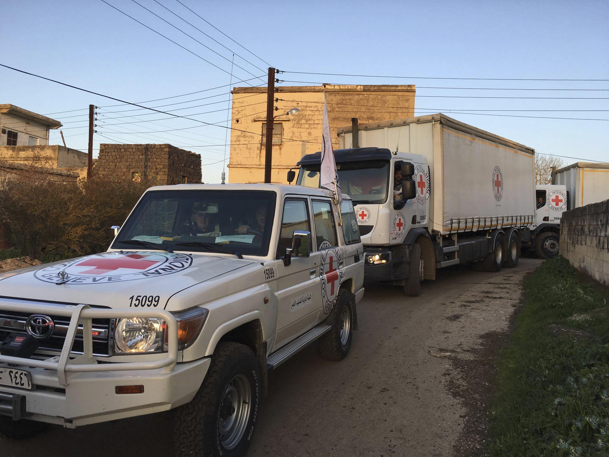 Au nord de Homs, région de Al-Houleh. Un convoi conjoint du CICR, du Croissant-Rouge Arabe syrien et des Nations Unies se rend dans plusieurs villages où il achemine des vivres, des médicaments et du matériel d'approvisionnement en eau pour plus de 70, 000 personnes. North of Homs, Al Houleh region. A joint convoy of the ICRC, the Syrian Arab Red Crescent and the United Nations reach several villages to deliver food and water supply equipment for more than 70, 000 people. Communiqué de presse sur le site web du CICR, 23.03.2016 : « Syrie : des secours parviennent enfin à plus de 70 000 personnes dans la région d'Al-Houleh. [...]. « La population d'Al-Houleh vit depuis longtemps dans des conditions très difficiles », a déclaré Majda Flihi, cheffe du bureau du CICR à Homs, qui a dirigé l'équipe du CICR à Al-Houleh. « Principalement agriculteurs, les habitants ne peuvent plus cultiver leurs terres, et leur bétail ne peut plus être nourri correctement parce que les champs sont aujourd'hui des lignes de front. » Le convoi de 27 camions transportait des vivres, du matériel pour réparer le système d'approvisionnement en eau, ainsi que des secours médicaux visant à soutenir la structure médicale du Croissant-Rouge arabe syrien, durement mise à l'épreuve, dans le village de Kafr Laha. Une équipe d'ingénieurs eau du CICR s'est aussi employée à améliorer l'état des puits qui constituent le seul approvisionnement régulier en eau potable. Un deuxième convoi, prévu dans les prochains jours, transportera des générateurs et des équipements pour assurer l'approvisionnement en eau. « Comme dans tous les lieux assiégés en Syrie, les civils tentent de survivre avec leurs maigres ressources. Ils ont besoin d'un approvisionnement régulier en vivres, en médicaments et autres types d'aide. Il nous faut un accès régulier, quelle que soit la situation sur le terrain », précise Mme Flihi. Al-Houleh vit en état de siège depuis 2012, et est le théâtre de violents combats depuis des mois. La réc